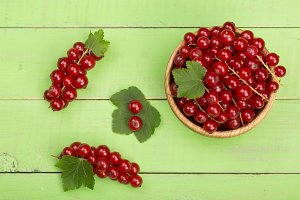 Red currant berries in a wooden bowl with leaf on the green wooden background. Top view