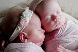 twin babies sleep in the crib in dresses