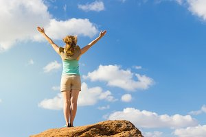 Woman with hands raised up. Blue sky