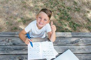 Smiling schoolboy at table gesturing