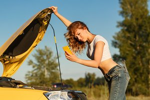 Girl repairing car and on phone