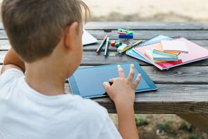 Schoolboy studying with tablet in garden