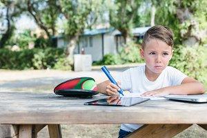 Pensive boy studying in backyard