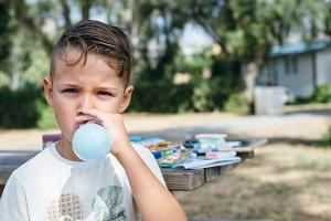 Kid blowing up balloon in garden