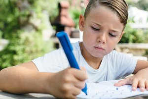 Concentrated schoolboy studying in garden