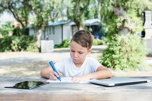 Boy drawing with pen in notebook