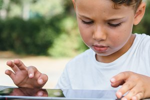 Adorable kid with tablet in backyard