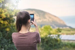 young woman photographing the landscape by smartphone camera