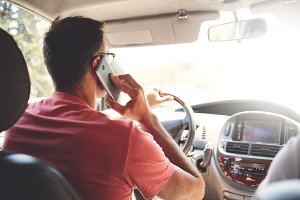man talks on the phone while driving a car