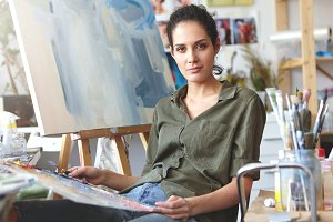 Picture of attractive professional young Caucasian female in casual clothes holding palette and painting knife working on oil painting, mixing colors, having inspired expression on her face