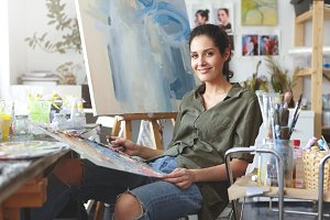 Indoor shot of beautiful female painter wearing shirt and jeans, sitting at chair, mixing colorful oils, making brush of strokes on easel. Female art-lover practicing drawing at her workshop