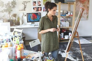 Art and inspiration. Indoor shot of hesitant young female artist wearing jeans and khaki shirt standing in spacious workshop interior in front of easel, evaluating painting that she just finished