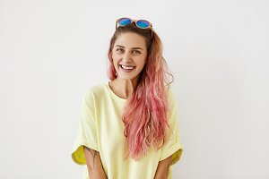 Trends, fashion and modern lifestyle concept. Pretty teenage girl with pleasant smile and long bushy hair with pink highlights posing in studio wearing yellow oversize t-shirt and shades on her head