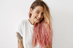 Style, fashion and hair coloring concept. Portrait of gorgeous young female with charming smile, tattoo on arm and long loose hair dyed pink looking at camera, having joyful carefree expression