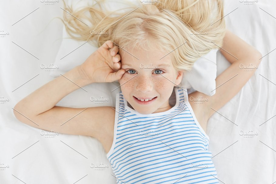 freckled blue eyed girl with blonde hair wearing striped t shirt