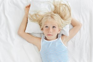 Thoughtful little girl with long blonde hair looking up, wearing striped shirt, lying on white pillow, dreaming about new bicycle. Restful adorable girl resting on white bed in children`s room