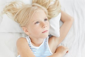 Pensive little girl with blue eyes and long eyelashes, having long blonde hair, wearing sailor T-shirt, lying on white pillow, looking aside while having dreams before sleep, dreaming about new toy