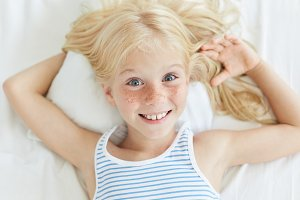 Cute little female child with blonde hair, blue eyes and freckled face, smiling joyfully while relaxing on bed, lying on white pillow. Small freckled girl in bed going to sleep. Children, lifestyle