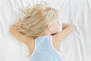 Blonde liitle girl sleeping on stomach, lying on comfortable pillow, having pleasant dreams. Small kid wearing striped shirt, having deep sleep at night. People, healthy sleep, lifestyle concept