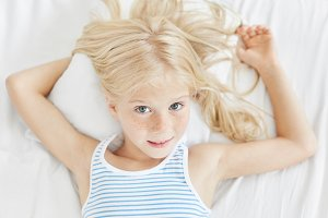 Lovely blue eyed freckled girl with light hair, wearing striped T-shirt, lying on white pillow in bedroom, going to fall asleep. Cute little female child relaxing in bed before sleep having comfort