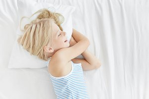 Pretty blonde girl in sailor T-shirt, lying on white pillow, smiling in sleep while seeing pleasant dreams. Restful female child sleeping after hard day playing with her friends. Children, relaxation