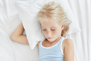 Pleasant looking little girl with blonde hair and freckled face, having sweet sleep while lying on white pillow closing eyes, enjoying calm atmosphere and comfortable conditions in her bedroom