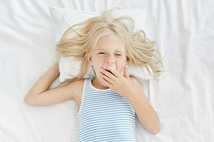 Sleepy girl waking up early in morning, covering mouth with hand while yawning, going to school or kindergarten. Blonde charming child in sailor T-shirt lying on white bed clothes, just awaking