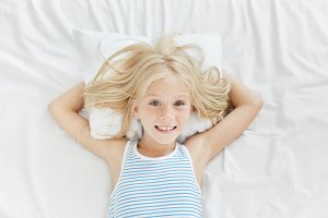 Lovely blue eyed female child with freckles, lying on white pillow, keeping hands behind it, smiling pleasantly into camera, being glad to see her parents in her bedroom. Little girl resting in bed