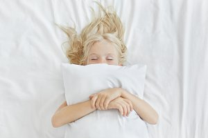 Carefree restful little girl lying on white bedclothes, embracing pillow while having pleasant dreams. Blonde girl with freckles sleeping in bed after spending all day at picnic. Restful child