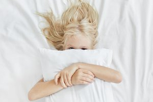 Sweet cute girl with light long hair, hiding behind white pillow, embracing it while lying in bed, having fun in morning. Playful child hugging pillow covering face with it. Health, sleep and children