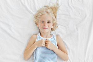 Cute girl with blonde hair, blue charming eyes and freckled face, wearing sailor T-shirt, lying on white bed cover, having glad expression after pleasant dreams at night. Children, relaxation