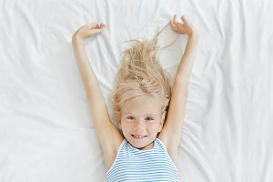 Lovely little child with blue eyes and freckles stretching in bed in morning, looking joyfully into camera, enjoying relaxation and wanting to start new day. Children, sleep and rest concept