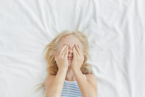 Portrait of little adorable girl with light hair, covering her eyes with hands while having fun and hiding from someone, laughing, lying on white bedclothes. Carefree child waking up in morning