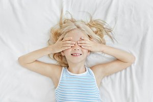 Adorable little girl lying on white bedclothes, covering her eyes with hands, wearing sailor T-shirt, smiling before sleep. Blonde kid with freckles having fun on bed not wanting to have sleep