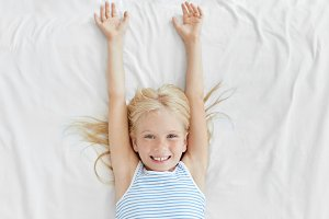 Adorable little girl with blonde hair and freckles, waking up in morning, stretching on white bedclothes, having pleasant smile after good sleep. Small kid smiling into camera while lying in bed