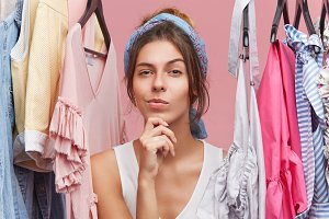 Portrait of thoughtful woman with scarf on head, standing near hangers with clothes, thinking over what to buy. Female shopaholic in boutique with pensive expression, having difficult choice