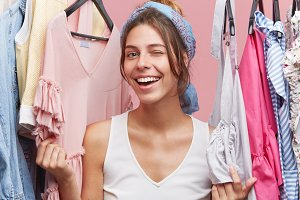 Happy female blinking eyes while standing near racks with clothes, having fun and positive emotions after successful shopping. Attractive woman in cloakroom posing in camera with joy and happiness