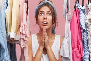 Pretty girl dressed casually standing among clothes hanging on rack in her dressing room, holding hands in prayer, having mounrful pathetic look, asking God to help her choosing dress for date
