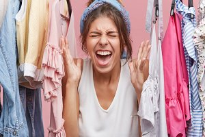 Beautiful woman screaming with negativeness, frowning her face being crazy because of clothes which hangs on hangers in her room. Stressful female looking mad while wanting to buy something new