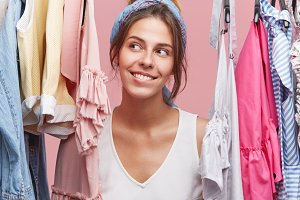 Lovely smiling female looking aside with cheerful expression, having good mood after successful shopping day, looking at her purchases while standing in her pink room. Woman looking at clothes