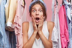 Adorable woman looking with great disbelief directly into camera, keeping hand on cheeks while standing in department store, choosing clothes, being surprised with very high prices on garment