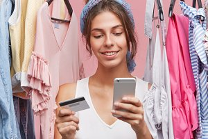 Indoor shot of beautiful woman with gentle smile, standing near variety of clothes being shopaholic, buying garment online, using smart phone and credit card. People, shopping, clothes concept