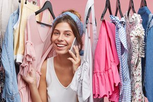 Style, fashion, shopping and consumerism. Excited charming young lady wearing headband speaking on mobile phone among trendy clothing items in dressing room of store, telling friend about final sale