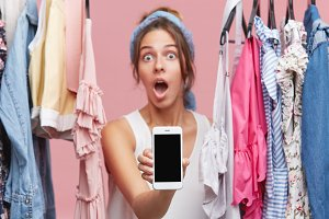 Portrait of beautiful woman looking with buuged eyes and widely opened mouth in camera, holding mobile phone in hands, standing between rack of clothes. People, shopping, clothes, buying concept