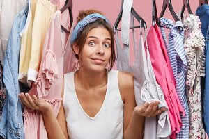 Female model in casual clothes, shrugging her shoulders while standing near her wardrobe, having hesitations what to wear. Pretty woman having nothing to wear. Clothing and fashionable people concept
