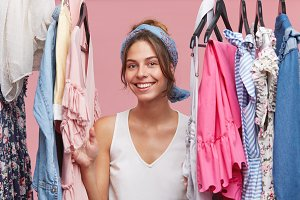 Positive smiling woman wearing white T-shirt and scarf, looking through clothes rail while standing in her fitting room, being glad to have many new fashionable clothes. Fashion and people concept