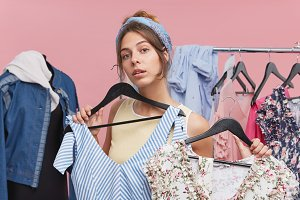 Cute young female standing against pink wall background in her bedroom, holding two different summer dresses deciding which one is more suitable to wear for a walk. People, clothing, style and fashion
