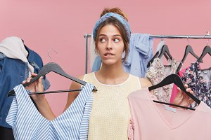 Cute female purchaser standing in fitting room, holding two stylish dresses, having difficult choice, biting her lips and looking aside with doubtful expression, needed advice what is better to buy