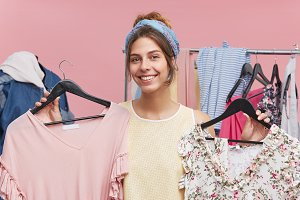 Cheerful female wearing scarf on head and shirt, smiling pleasantly while holding hangers with two dresses, being glad to buy both of them in clothes shop. Female seller advising to buy dress