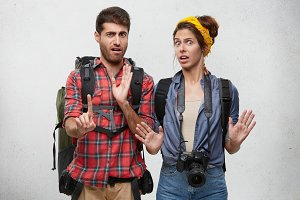 Studio shot of emotional bearded guy and beautiful girl with professional camera gesturing with both hands, making stop sign, expressing denial, reject, unwillingness. Human emotions and feelings